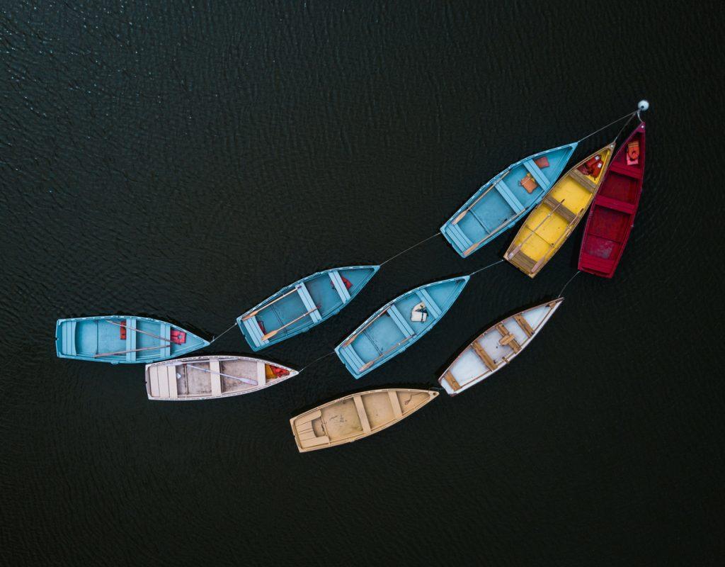 barche in mare legate da una corda ad un punto in alto a destra
