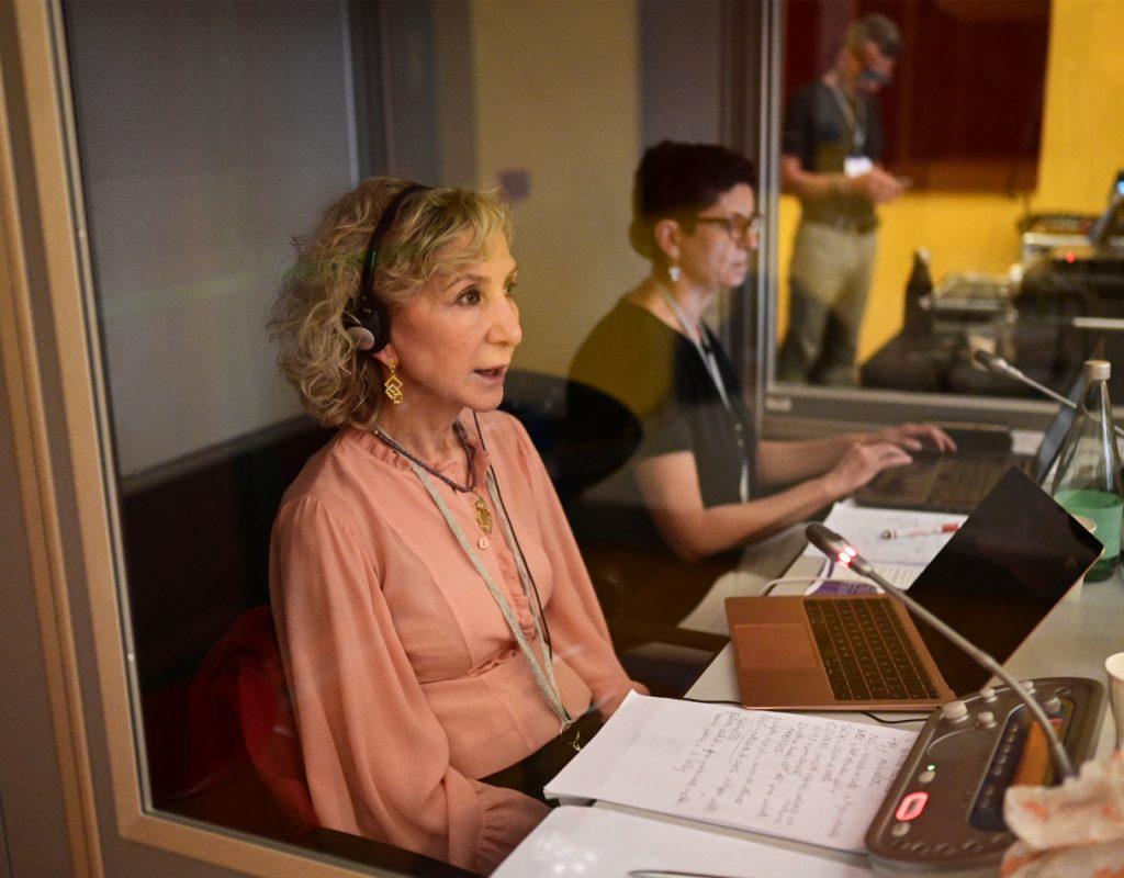 interprete a lavoro, seduta in cabina di traduzione con con cuffie in testa