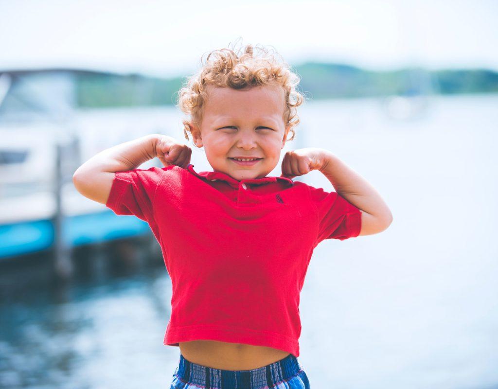 bambino in primo piano che mostra i muscoli sorridendo
