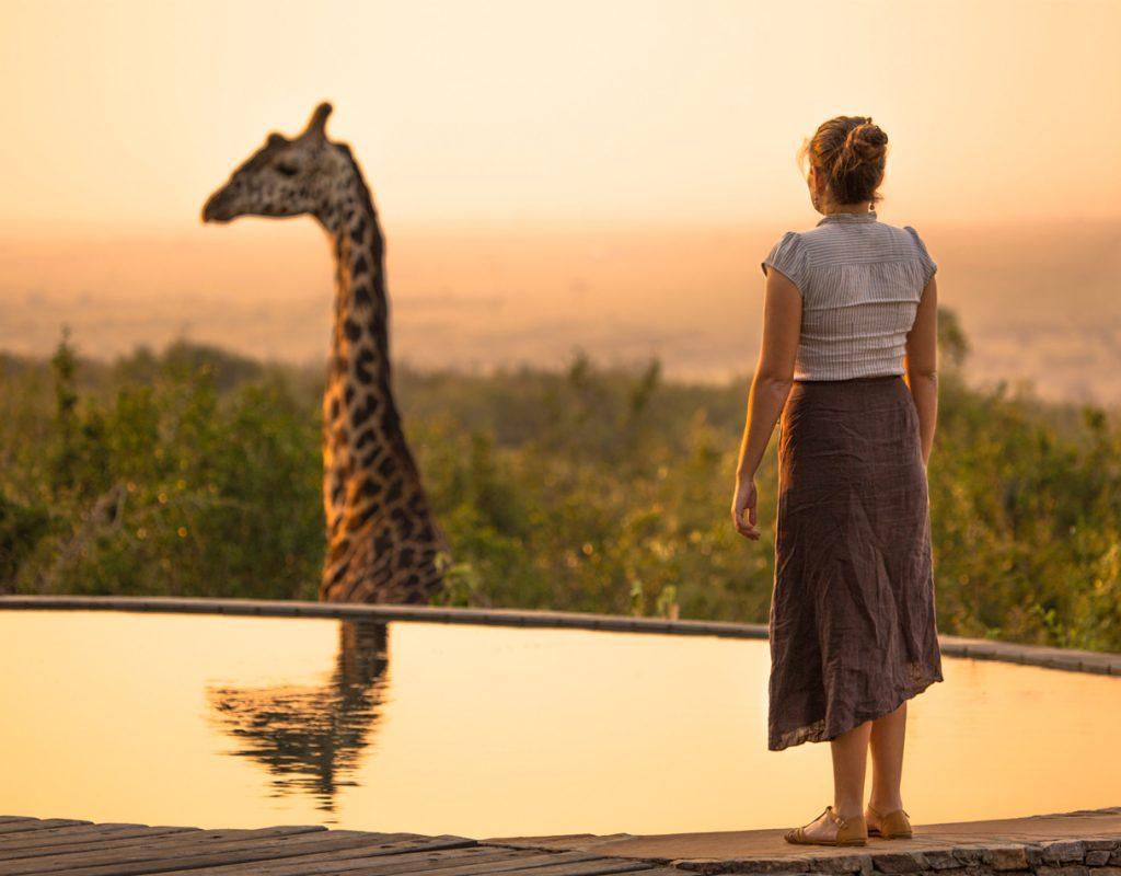 Donna di schiena di fronte a una piscina con una giraffa sullo sfondo