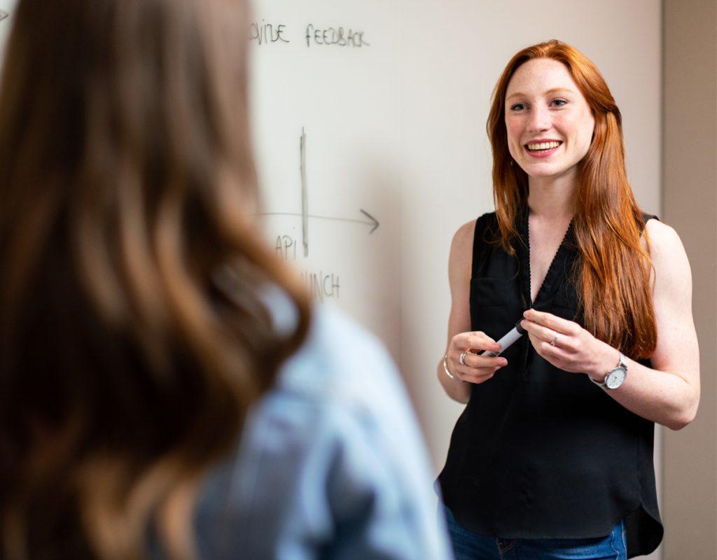 donna con un pennarello in mano che sorride verso un'altra di schiena in primo piano